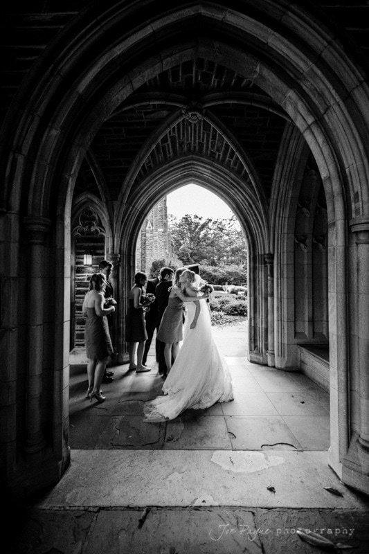 bridesmaid congratulates the bride at duke chapel